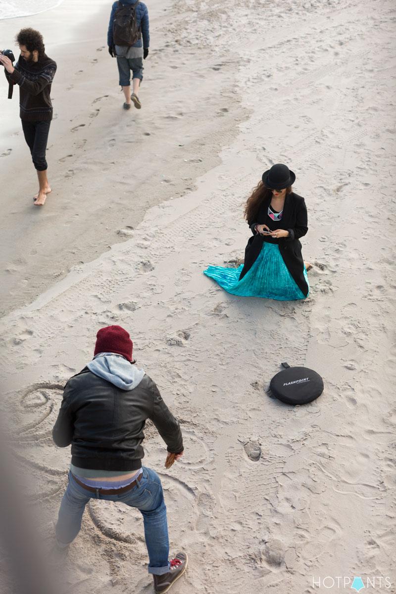Funny girl jumping sand ocean bowler hat aviators